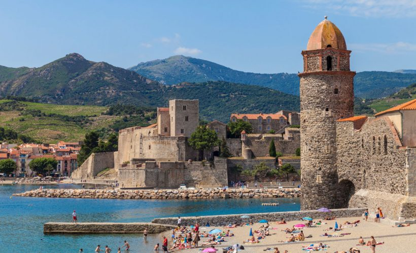 Collioure, France - July 01, 2016. View of the picturesque Collioure, situated in the Département Pyrénées-Orientales. Château Royal in the centre, lighthouse/spire on the right side. The beach is highly frequented by tourists and natives. Pyrenees Mountain Range in the background.
